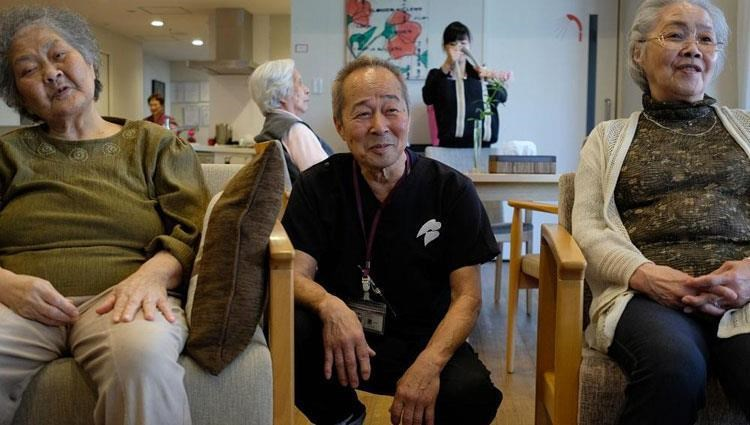 Japanese doctor sitting with an old man