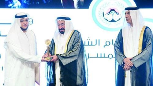 سلطان القاسمي يسلم جائزة تكريم سلطان النيادي الشخصية المحلية المكرمة وتسلمها عنه الفنان ياسر النيادي (الصور من وام)