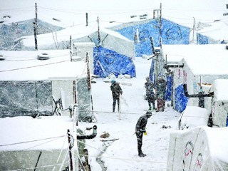 Syrians stand between their tents as they prepare to remove the snow from the top of their tents at a refugee camp in Deir Zannoun village, in the Bekaa valley, east Lebanon, Wednesday, Jan. 7, 2015. While the storm disrupted life for everyone, it proved